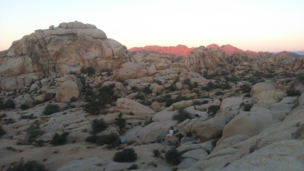 Tiny campers nestled in the rocks, and a red sunrise
